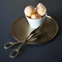 Sobremesa deliciosa com recheio de creme. colocado em uma tigela branca em uma bandeja de bronze antigo. lindas pinças de bronze para servir. gastronomia foto
