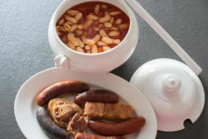 saborosa fabada asturiana caseira, tigela com o feijão e acompanhamento com carne, compota, chouriço e chouriço. gastronomia tradicional das astúrias, espanha. foto