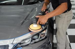 detalhamento de carro - mecânico masculino segurando a máquina de polir de carro. indústria automobilística, polimento de automóveis e oficina de pintura e reparação. foto