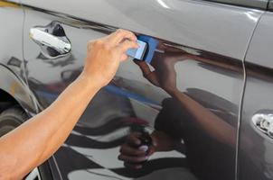 detalhes do carro. um mecânico está aplicando um revestimento de vitrocerâmica no carro da oficina. foto
