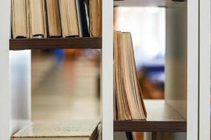 muitos livros em pé e deitados nas prateleiras foto