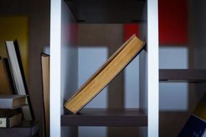 livro em pé na diagonal na prateleira em fundo escuro e desfocado foto