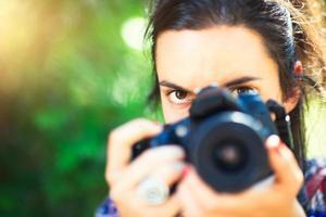 garota fotógrafa olha para ela antes de fotografar foto