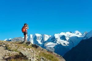 garota fotografa altas montanhas dos Alpes foto