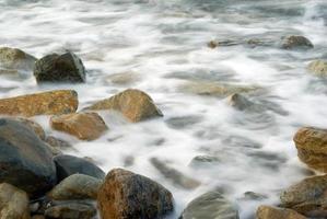 turbulência água do mar e rocha na costa foto