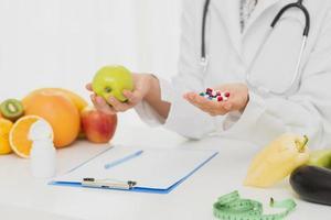 médico com comprimidos e frutas frescas foto
