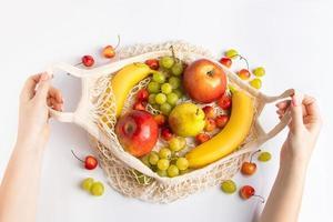as mãos das mulheres estão segurando uma bolsa de malha ecológica com frutas. comida vegana orgânica. desperdício zero e conceito de estilo de vida sustentável. foto