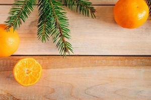 moldura feita de galhos de pinheiro e tangerinas em fundo de madeira. decoração de natal. foto