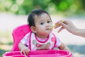 retrato de família da mãe alimentando seu bebê de 7 meses. conceito de tempo de qualidade da vida cotidiana com atividade alimentar em criança recém-nascida. foto