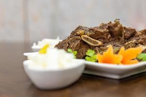 o prato de carne está no prato na mesa de madeira foto