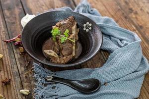a comida feita de carne bovina está na tigela sobre a toalha da mesa de madeira foto