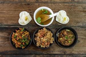 comida de carne e acompanhamentos estão na mesa de grãos de madeira foto