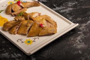 o pato amarelo no longo prato branco está na mesa de madeira foto