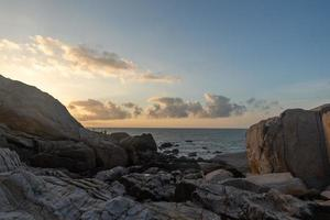 pela manhã, o sol brilha nas rochas e as ondas da praia foto