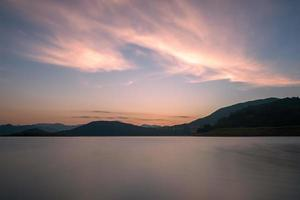o lago noturno refletia as montanhas e o céu em ambos os lados foto