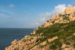 pedras de várias formas intemperizadas pelo mar sob o céu azul foto