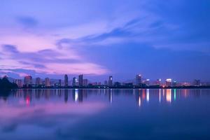ao anoitecer, o lago reflete a visão noturna da cidade foto