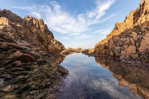 a água do mar entre os recifes à beira-mar reflete os recifes amarelos e o céu azul foto