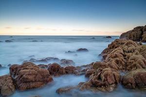 água do mar e recifes à beira-mar sob o céu azul foto