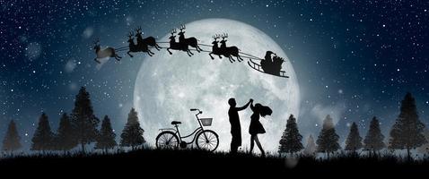 silhueta do Papai Noel à noite de Natal com casal dançando sob a lua cheia. foto