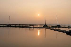 ao nascer do sol da manhã, a água do mar reflete o barco pesqueiro foto