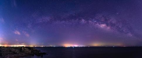 o céu estrelado à beira do mar e a via láctea foto