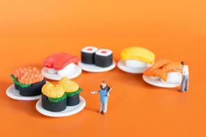 pequeno chef fazendo sushi em fundo laranja foto