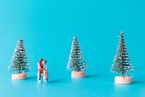 pessoas em miniatura, casal apaixonado sentado ao lado de uma árvore de natal foto