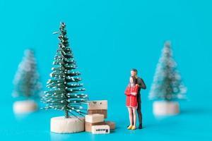 pessoas em miniatura, casal apaixonado em pé ao lado de uma árvore de natal foto