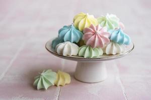 pequenos merengues coloridos no suporte de cerâmica foto