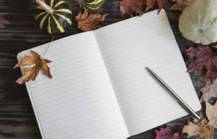 abóboras e folhas quadro com notebook em fundo de madeira. foto
