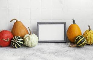 porta-retrato e decoração de abóbora em cima da mesa sobre o fundo de azulejos brancos. foto