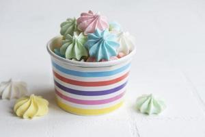 pequenos merengues coloridos na tigela de papel foto