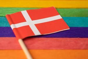 bandeira da Dinamarca no fundo do arco-íris símbolo da bandeira do movimento social do mês do orgulho gay lgbt a bandeira do arco-íris é um símbolo de lésbicas, gays, bissexuais, transgêneros, direitos humanos, tolerância e paz. foto