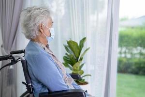uma mulher idosa sentada em uma cadeira de rodas, olhando pela janela esperando alguém. tristemente, melancólico e deprimido. foto