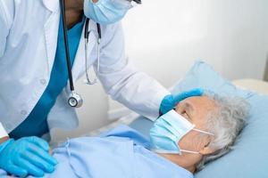 médico ajuda paciente asiático sênior ou idosa idosa usando uma máscara facial no hospital para proteger a infecção de segurança e matar o coronavírus covid-19. foto