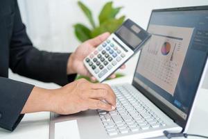 contador asiático trabalhando e analisando contabilidade de projeto de relatórios financeiros com gráfico gráfico e calculadora no conceito moderno de escritório, finanças e negócios. foto