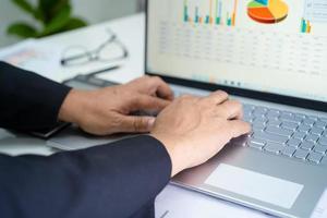 contador asiático trabalhando e analisando contabilidade de projeto de relatórios financeiros com gráfico gráfico no conceito moderno de escritório, finanças e negócios. foto