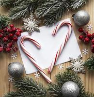 fundo de madeira de natal, cartão com decoração de natal, bastões de doces de natal, bolas de natal e galho de abeto, foto
