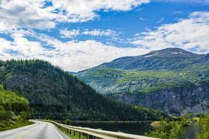 dirigindo pela Noruega no verão com as montanhas e vista para o fiorde foto