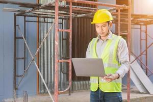 um engenheiro examina a planta baixa do canteiro de obras. foto