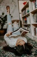 foto vertical de uma jovem do sul da Ásia deitada no tapete e lendo um livro