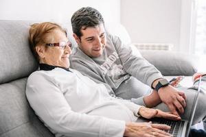 homem alegre e mulher sênior usando laptop juntos foto