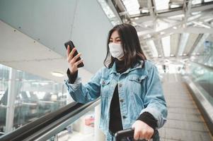 viajante asiática usando máscara usando smartphone em pé na escada rolante foto