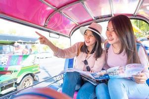 Mulher asiática em um passeio turístico de tuk tuk táxi foto