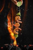 espetos de camarão e mexilhão grelhados sobre o calor do carvão em fogo e fumaça de fundo. natureza morta, anúncio de comida foto