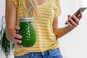 mulher caucasiana, segurando o frasco de smoothie vegan verde com canudo de metal. conceito de dieta alcalina. foto