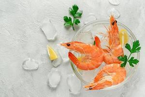 camarões resfriados em uma tigela com gelo, limão e salsa em fundo cinza. comida italiana, copie o espaço. foto