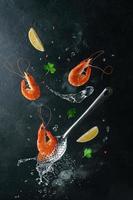 camarões tigre voando com ingredientes sobre a escumadeira e água fervida. design criativo de culinária de frutos do mar foto