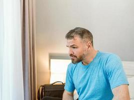 homem bonito infeliz sentado sozinho na cama no quarto. divórcio, insônia, depressão, problemas foto
